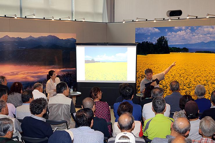 国内の絶景を収めた写真を解説する石川さん(奥右)