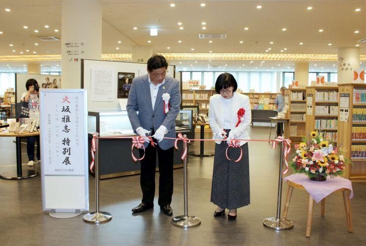 作家の故火坂雅志さんの直筆原稿などを集めた特別展のテープカットをする、妻の中川洋子さん(右)と林茂男・南魚沼市長=同市図書館