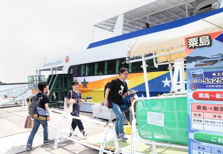 粟島発新潟行きの最終便に乗船する観光客ら=21日、粟島浦村