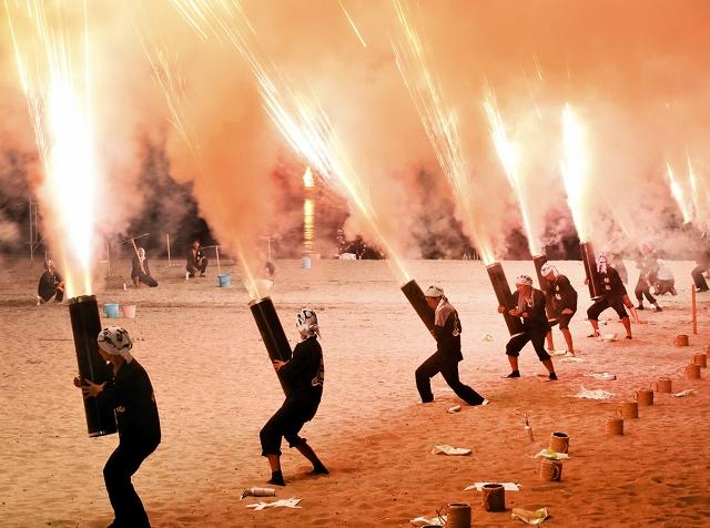 玩具花火を使った迫力あるパフォーマンスで観衆を魅了する櫓龍=2018年7月、福井県高浜町の若宮海水浴場