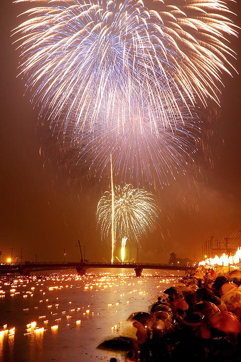 雨空を染めた花火。「火流し」で川面も幻想的に彩られた=白岩川河口付近(多重露光)
