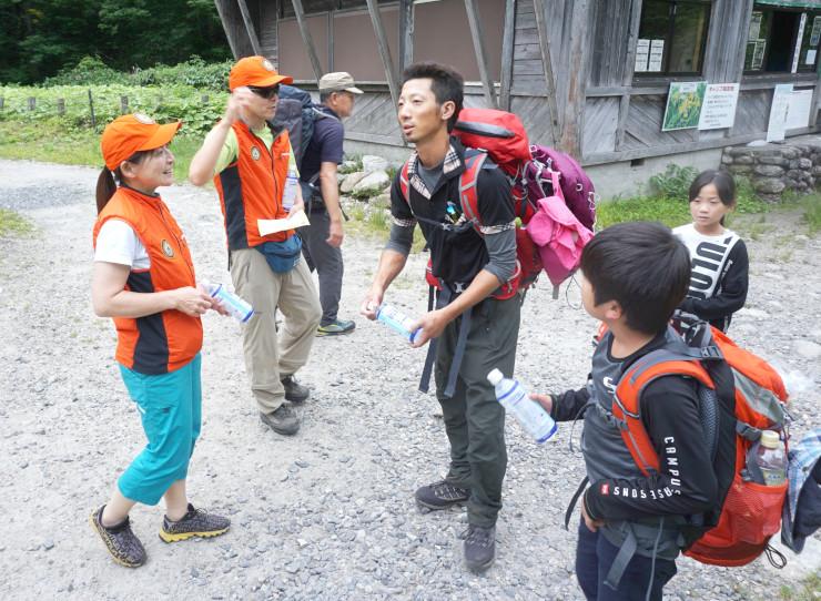 経口補水液のペットボトルを登山者に渡し、水分補給を呼び掛ける大城さん(左)ら