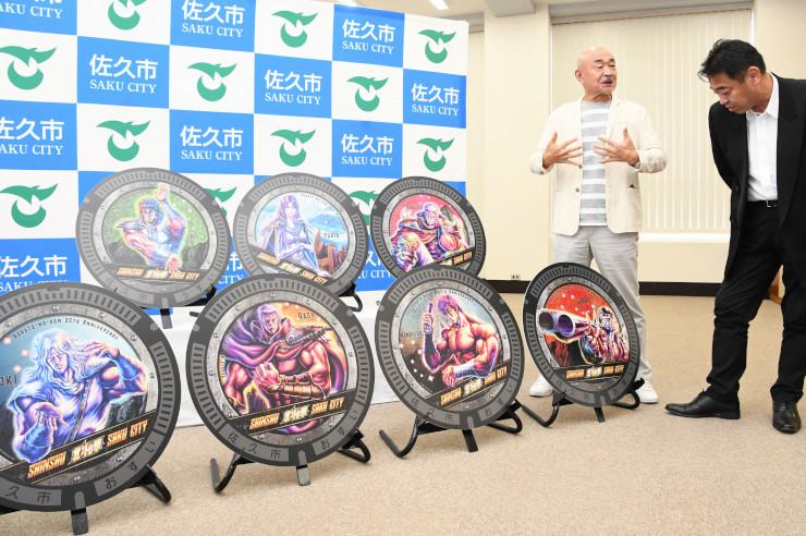 発表したデザインを前に話す武論尊さん(右から2人目)と柳田市長