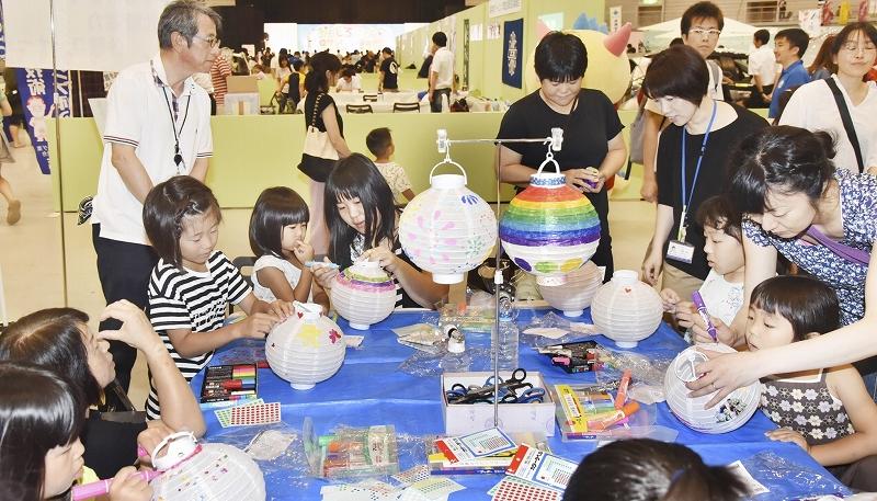 工作を楽しむ親子ら=7月27日、福井県のサンドーム福井