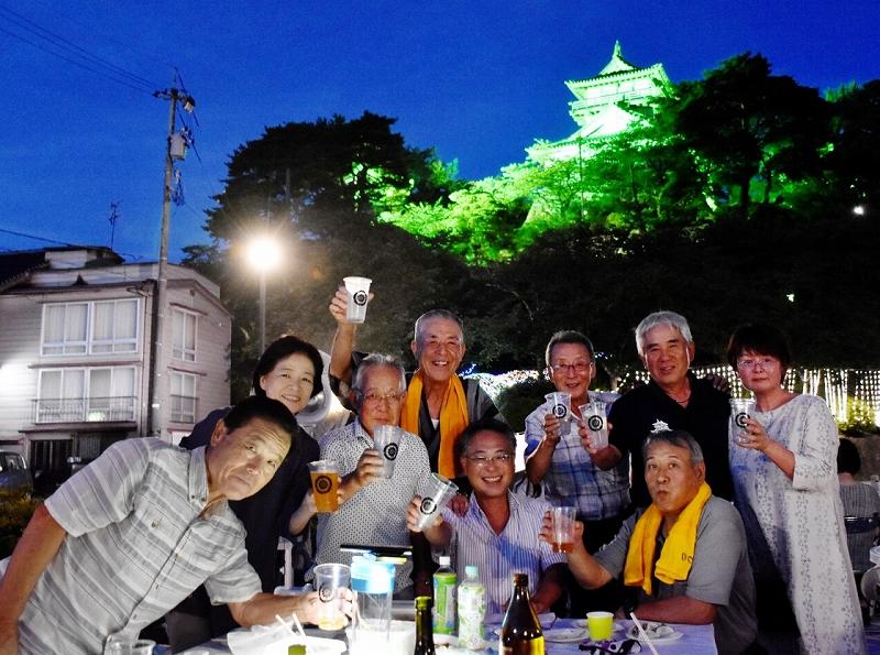 ライトアップされた丸岡城を背に乾杯する来場者=7月26日夜、福井県坂井市のお天守前公園