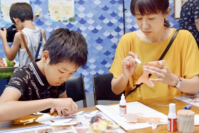自分の顔写真が印刷された金魚のペーパークラフトを組み立てる親子=7月27日、福井県福井市の県立美術館