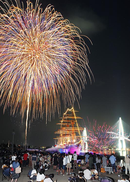 帆船海王丸と新湊大橋の上空に打ち上げられた色鮮やかな花火=海王丸パーク