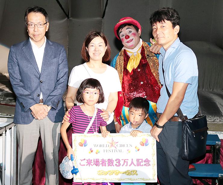 3万人目の来場者の今牧義耀ちゃん(前列右)と家族ら=富山市下飯野の富山市民球場駐車場特設大テント