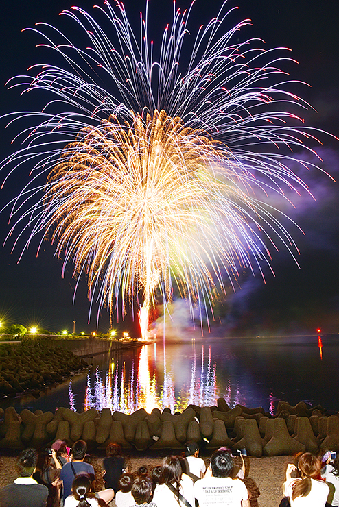 夜空と海面を鮮やかに染める花火