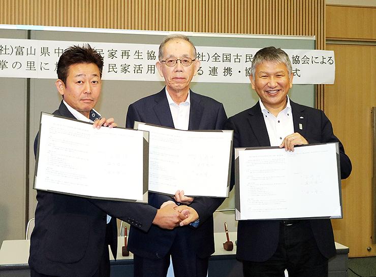 協定を締結し、握手を交わす山崎理事長(中央)や古民家再生協会の代表者