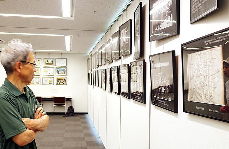 戦争の爪痕を伝える写真を見つめる来場者=県民会館