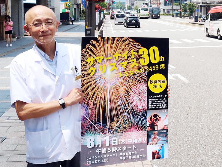 会場となる平和通りで、イベントをPRする鈴木理事長。後方の空に花火が打ち上げられる