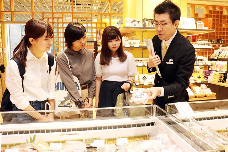 日本橋とやま館で田崎館長代理(右)から説明を受けるボランチの学生