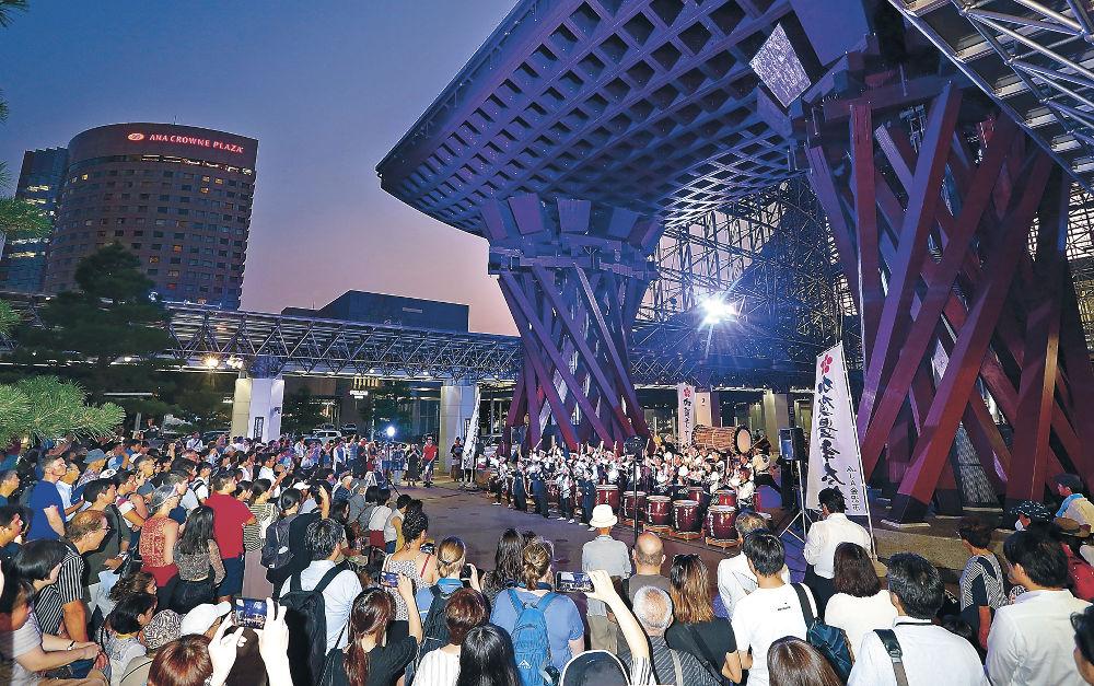 五彩に輝く鼓門の下で和楽器演奏を楽しむ駅利用者=金沢駅東広場