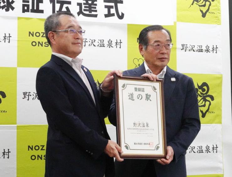 登録証を富井村長(右)に手渡す塩谷所長