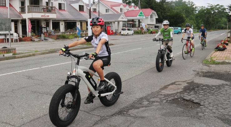 電動アシスト機能が付いたスポーツ自転車で走る金子さん一家