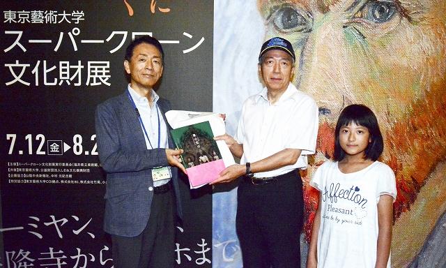 山埜館長(左)から記念品を受け取る男性と孫の女児=8月1日、福井県福井市の県立美術館