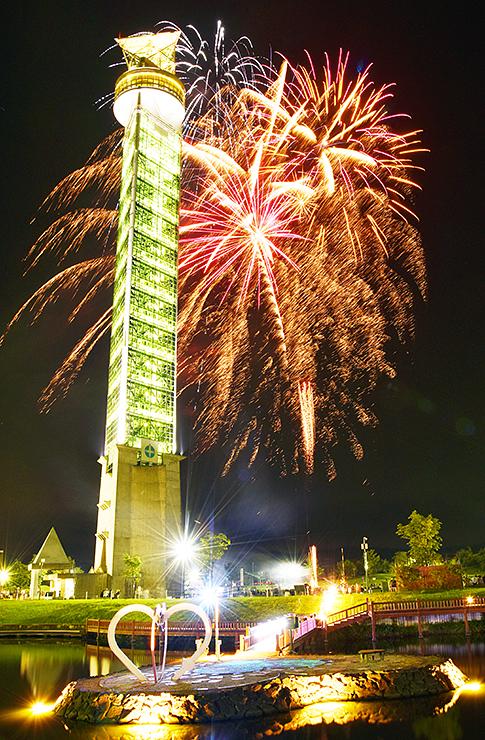 ライトアップされたクロスランドおやべのタワーとともに夜空を彩る花火