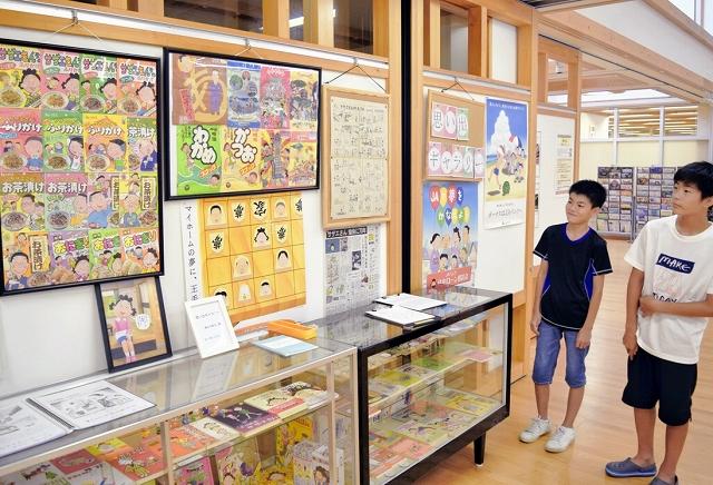 「サザエさん」関連の本やポスターなどが並ぶ展示会=福井県おおい町里山文化交流センター