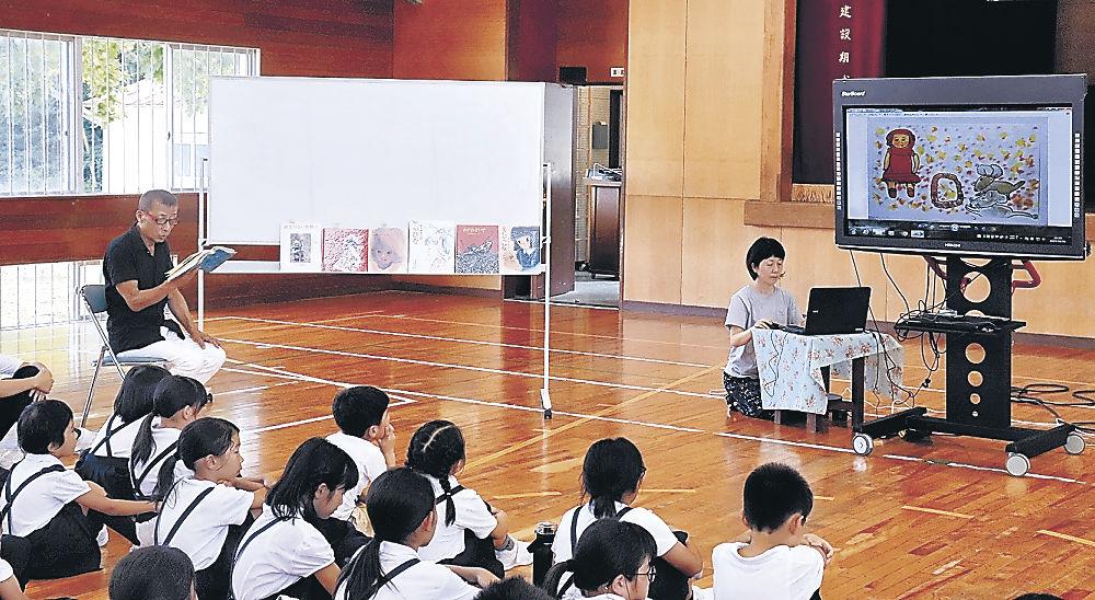 紙芝居を披露する山村さん(左)=加賀市南郷小