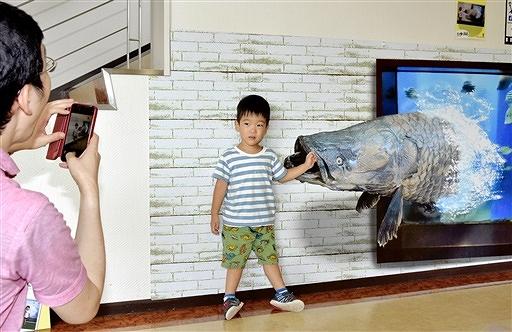 ピラルクに襲われているような構図で写真撮影する親子=8月4日、福井県高浜町青戸の「若狭たかはまエルどらんど」