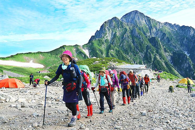 剱岳をバックに景色を眺めながら歩く団体登山客 =剱沢キャンプ場