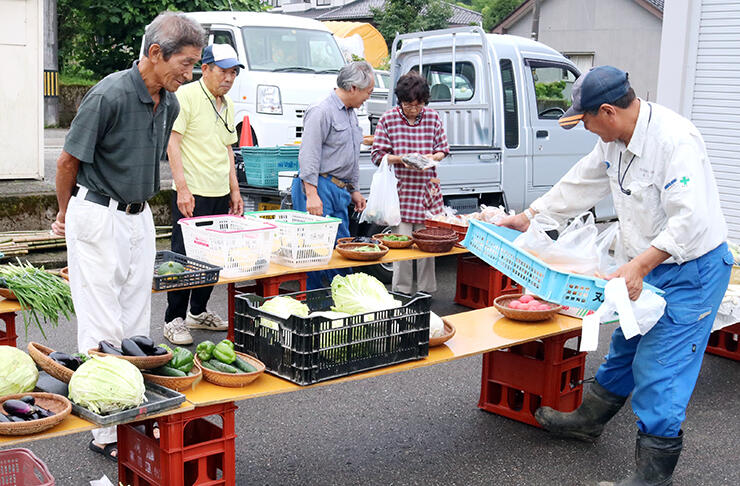 7月の青空市で野菜などを並べる住民