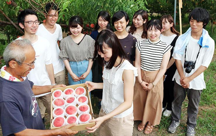 小倉社長(左)からモモを受け取る品田さん