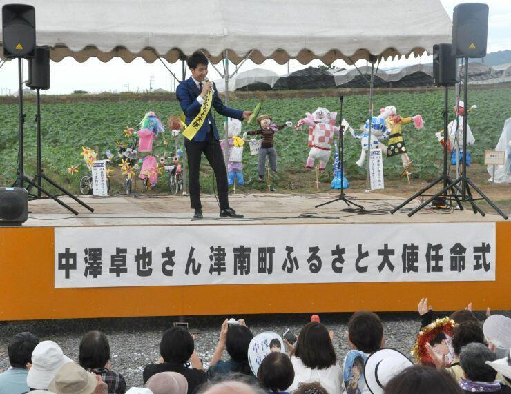 ふるさと大使の任命式で、特産のスイートコーンを手に歌う中沢卓也さん=津南町「ひまわり広場」