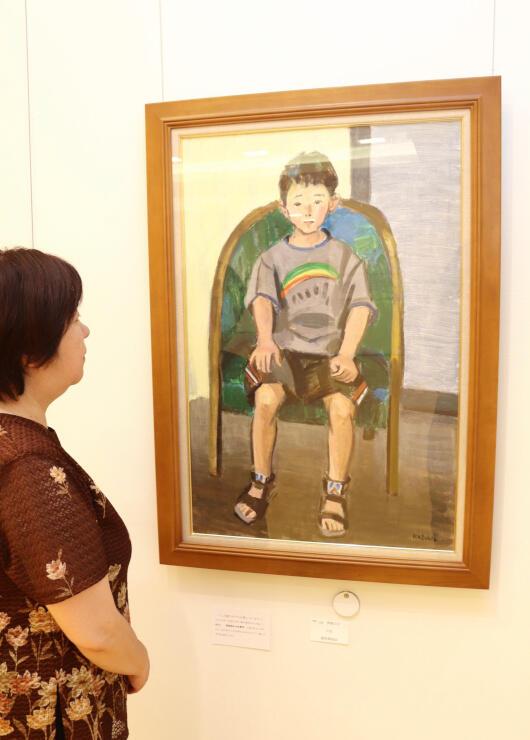 川上さんが描いた少年の絵を見つめる三宅さん。モデルになった人を探している