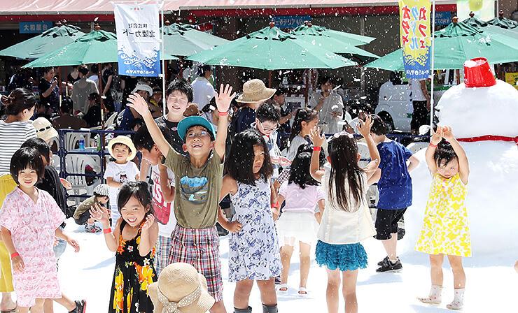 人工降雪機から吹き出す雪に手を上げて喜ぶ子どもたち