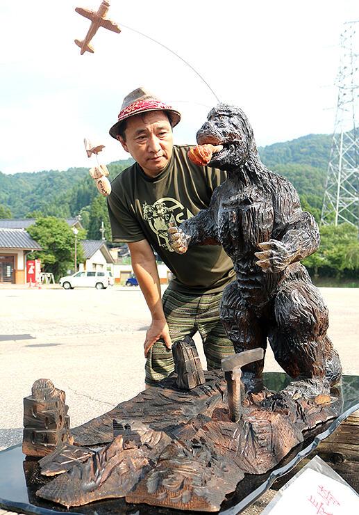 ゴジラの彫刻を見つめる音琴さん=いなみ木彫りの里