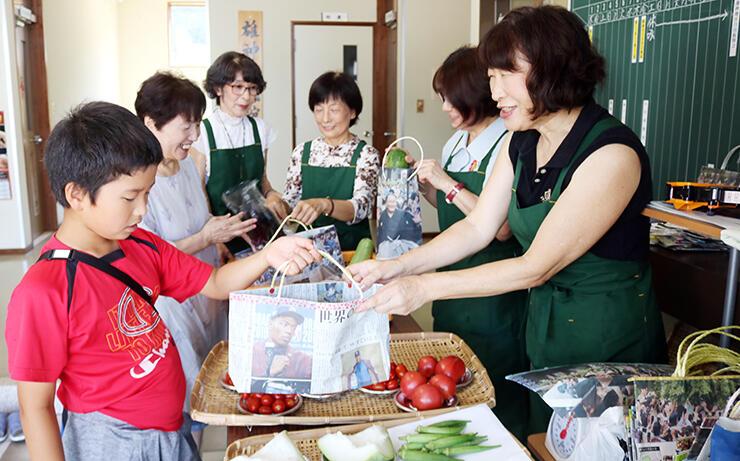 野菜をエコバッグに入れて販売するメンバー