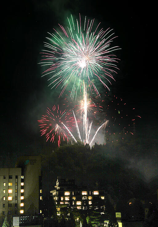 温泉街の夜空を彩る大輪の花火(黒部市宇奈月温泉のサン柳亭屋上から撮影、多重露光)