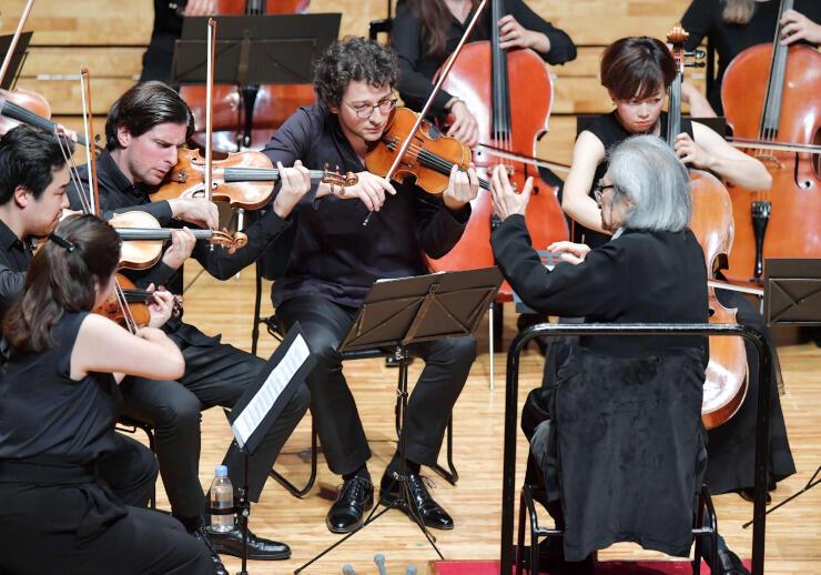椅子に腰掛けて若手演奏家らを指揮する小澤さん=18日、ザ・ハーモニーホール