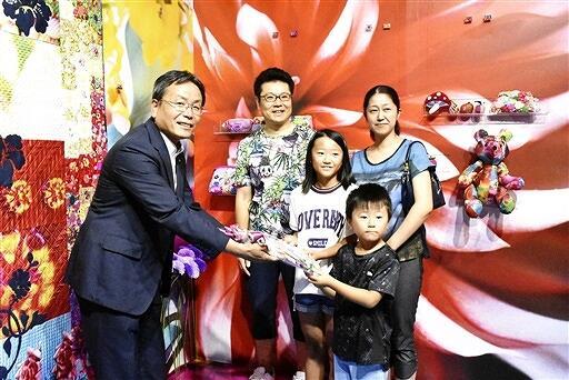 大代理事長(左)から記念品を受け取る一家=8月18日、福井県あわら市金津創作の森