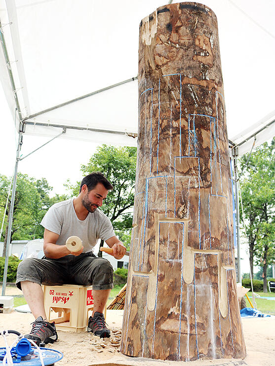 丸太にのみを打つロペスさん=井波芸術の森公園