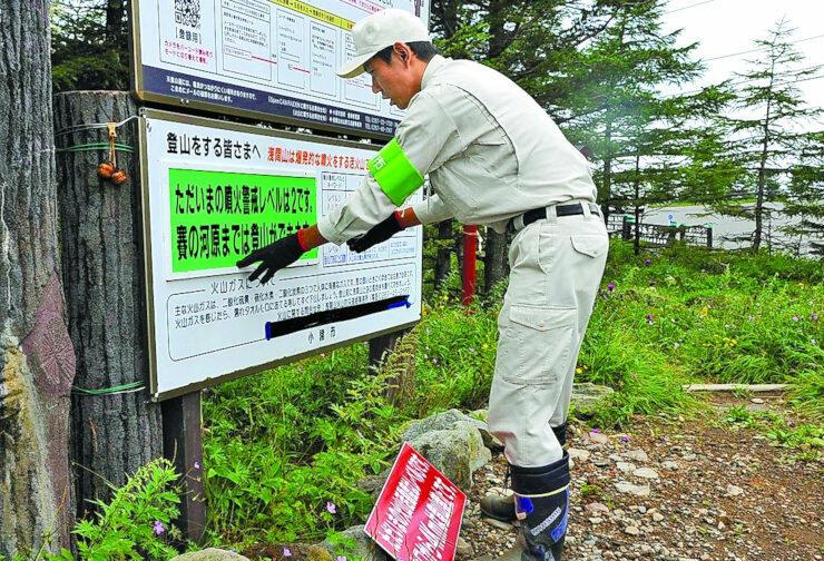 長野、群馬県境の車坂峠登山口で、登山者に向けた看板を付け替える小諸市職員=19日午前11時7分