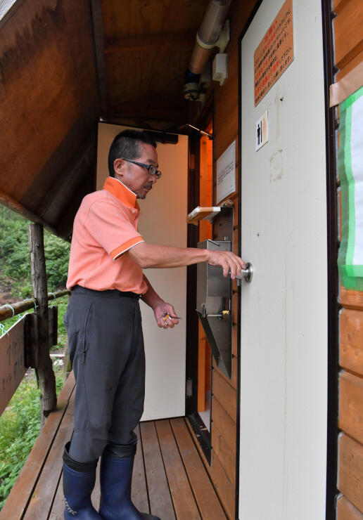 登山道規制の緩和で、火山館近くにあるトイレを点検する館長の神田さん=19日午後3時46分