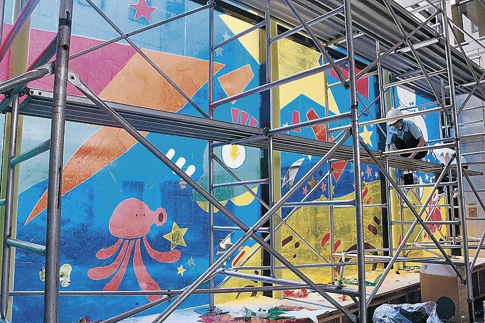 窓ガラスをカラーセロハンで彩る学生=市立病院