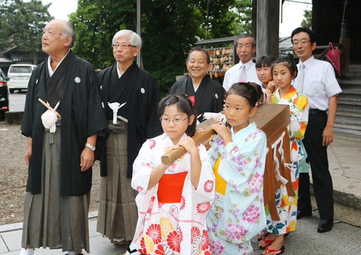 ご神体が入った櫃を運び出す女子児童ら=高岡関野神社