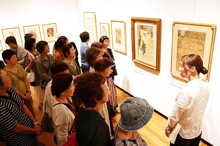 宝田副主幹学芸員(右)の説明を聞きながら、ミュシャの作品を鑑賞する参加者