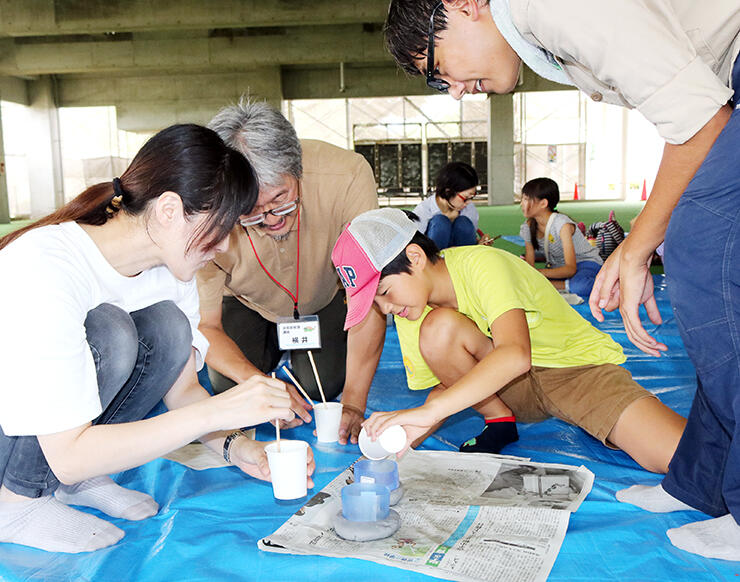 粘土の型に石こうを流し込み、化石レプリカを作る親子
