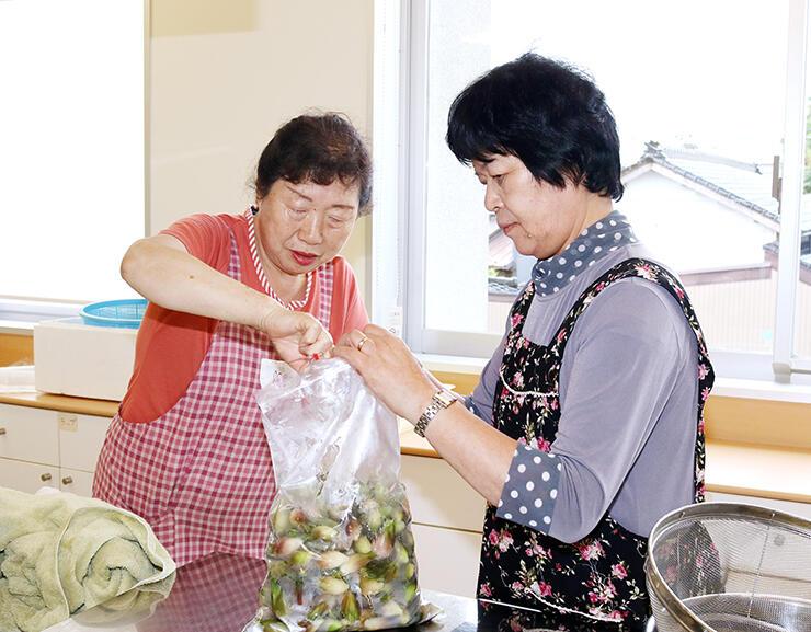 ミョウガに酢を注ぐメンバーと河合会長(右)
