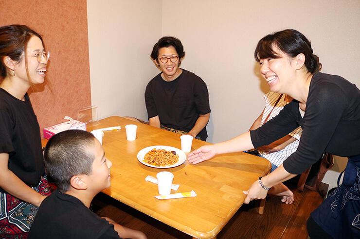 試食のパスタを運ぶ田中麻紗子さん(右)