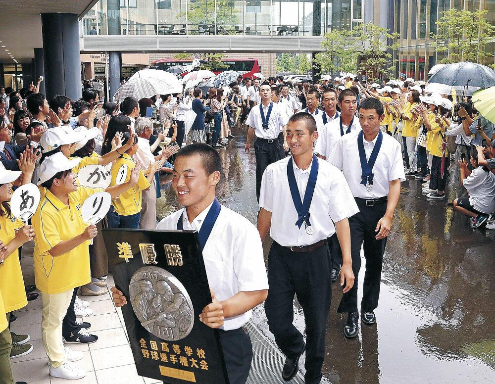 母校に戻り、関係者の歓声に迎えられる選手たち=金沢市