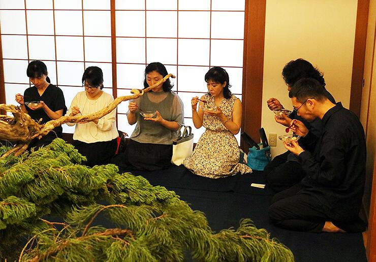 樹木の造形を前に、もてなしを受ける参加者