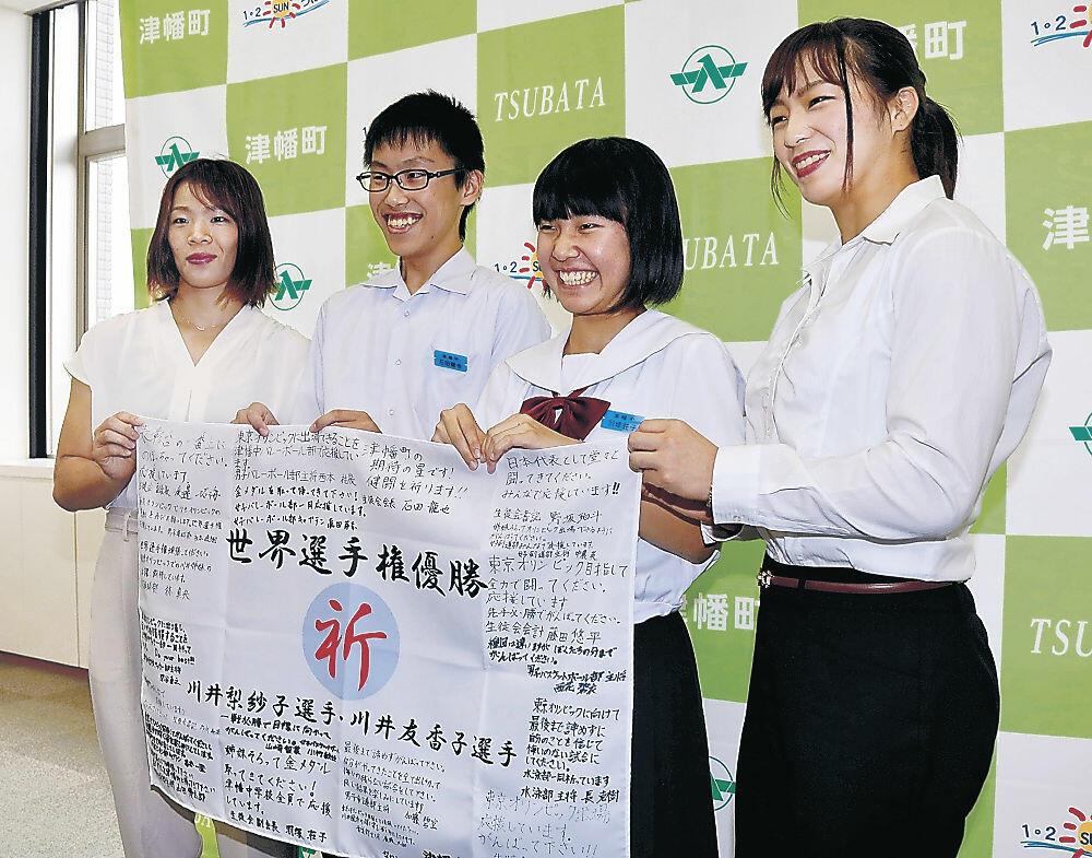 津幡中生徒会から贈られた寄せ書きを手にする川井梨紗子(左端)、友香子(右端)の両選手=津幡町役場