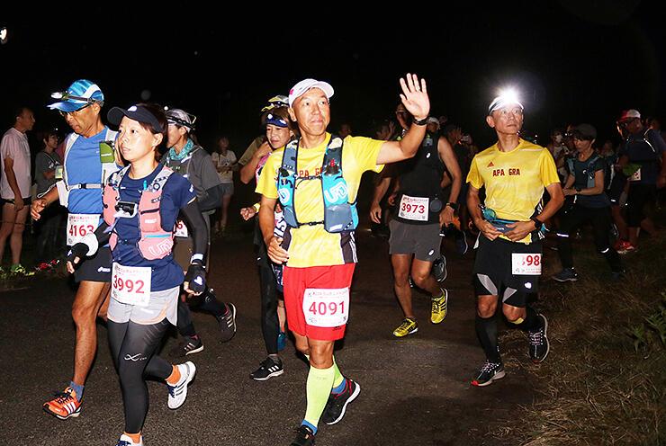 声援を受けながら、続々とスタートを切る出場者=24日午前4時、浜黒崎海岸