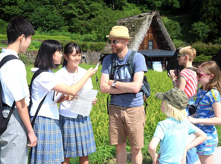 相倉合掌造り集落で外国人観光客を案内する部員(左3人)